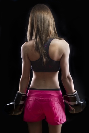 Beautiful woman kick boxing over dark background photo