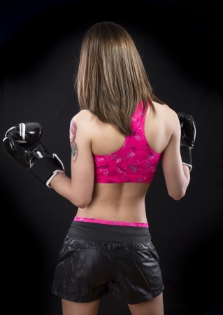 A sexy young and fit female fighter posing in combat poses photo