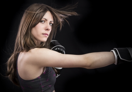 boxer woman during boxing exercise making direct hit with black gloves photo