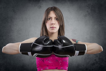 Young beautiful woman with boxing gloves at workout over rusty background photo