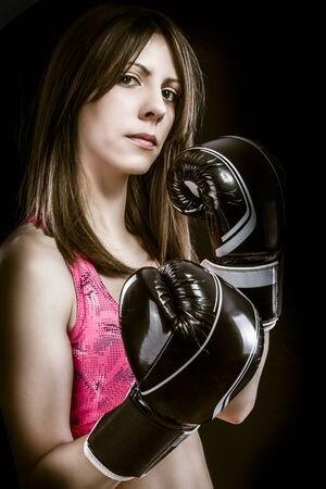 Boxing woman, pretty young boxing  and defending by hands  black box gloves photo