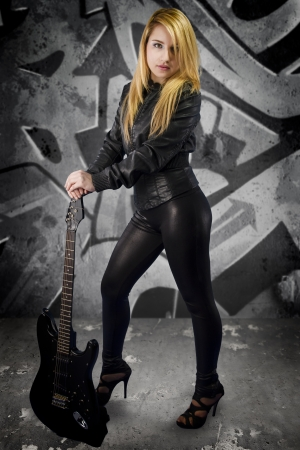 Sexy young blonde dressed in black leather with electric guitar on grafitti background photo
