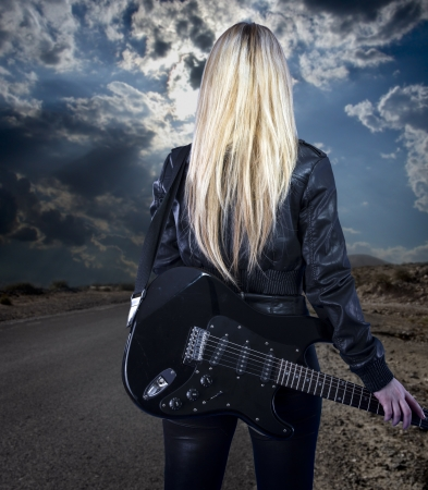 Beautiful young blonde dressed in black leather with electric guitar walking in a desert road