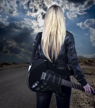 femme avec guitare: Belle jeune blonde habill�e en cuir noir avec guitare �lectrique marche dans une route du d�sert Banque d'images
