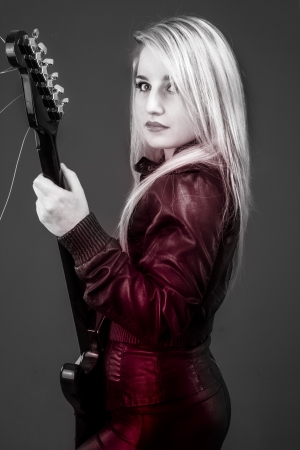 young beautiful blonde with red light, electric guitar photo