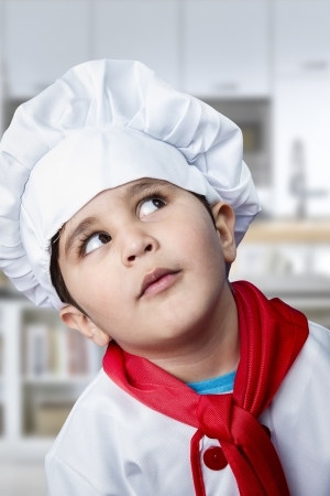 Funny boy dressed in chef, cooking in a kitchen photo