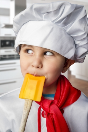 Funny boy dressed in chef with orange spoon in mouth