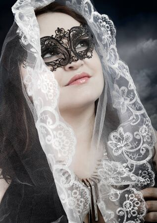 religious woman with white veil in a position to pray photo