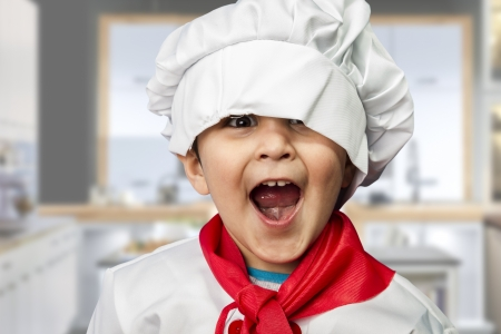niños cocinando: Niño divertido vestido como un cocinero Foto de archivo