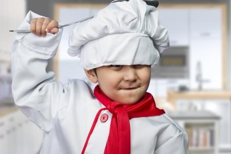 Drôle enfant habillé comme un cuisinier avec un pan de frapper la tête Banque d'images - 19379377