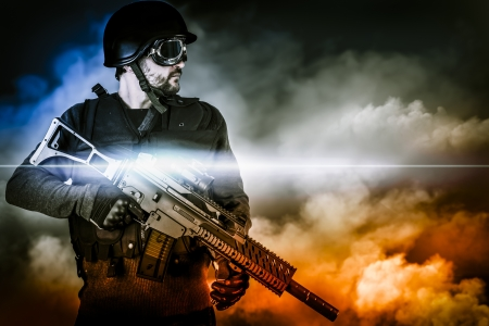 face guard: assault soldier with rifle on apocalyptic clouds Stock Photo