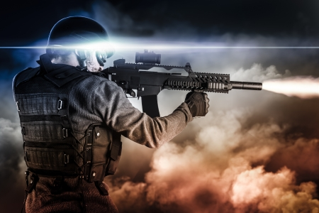 people force: assault soldier with rifle on apocalyptic clouds, firing Stock Photo