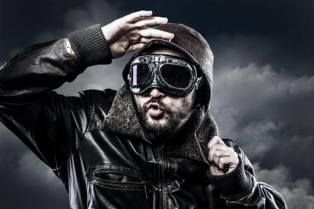 面白い表現で眼鏡とヴィンテージの帽子を持つパイロット 写真素材