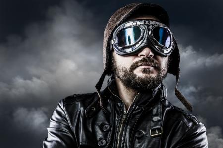 誇らしげな顔と眼鏡とビンテージの帽子を持つパイロット
