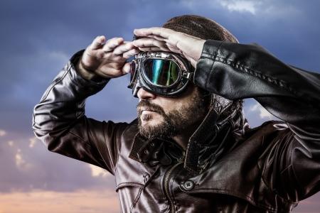 地平線を見て誇りに思って式と眼鏡とビンテージの帽子を持つパイロット