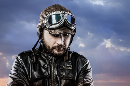adventure aeronautical: pilot with glasses and vintage hat with proud expression over cloudscape