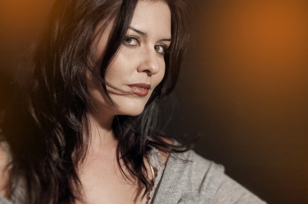 brunette posing with grey silk shirt and transparencies photo