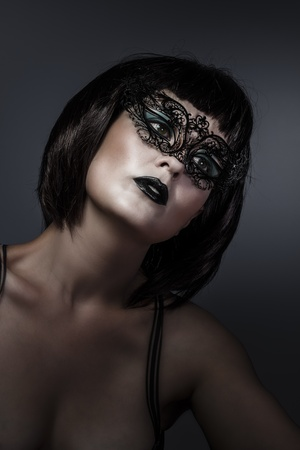 Doll, beautiful brunette with short hair and Venetian mask, cabaret photo
