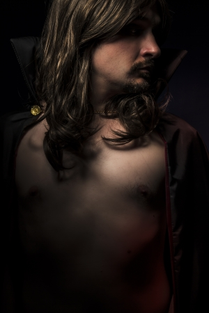 Vampire with black coat and long hair, nude photo