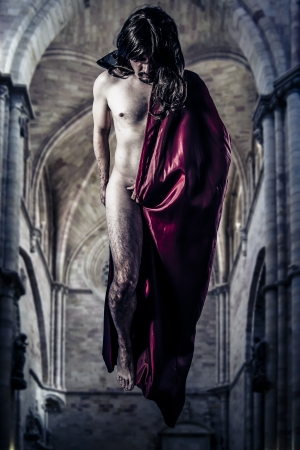 Nude magician levitating inside a Gothic cathedral photo