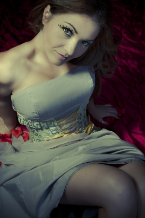 red bed: Attractive woman looking at camera, blonde, lying on red bed