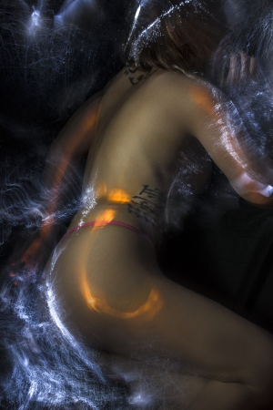 tattoed: Artistic  , tattoed woman lying with fiber optics and light effects on her skin Stock Photo