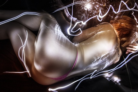 Artistic  , tattoed woman lying with fiber optics and light effects on her skin photo