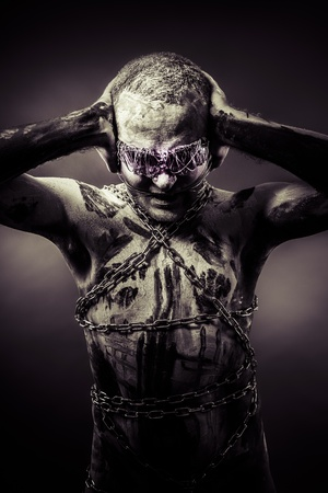 Young covered in bandages and wounds, chained photo