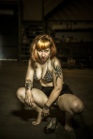 Hunter, sensual tattoed woman in an industrial area photo