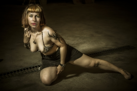 Danger, sensual tattoed woman in an industrial building photo