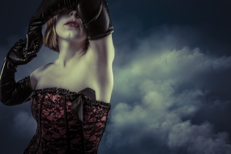 Portrait of a beautiful blonde woman with corset over cloudy background photo