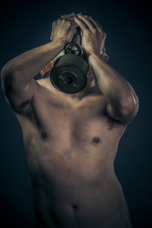 Industrial concept, nude man with gas mask photo