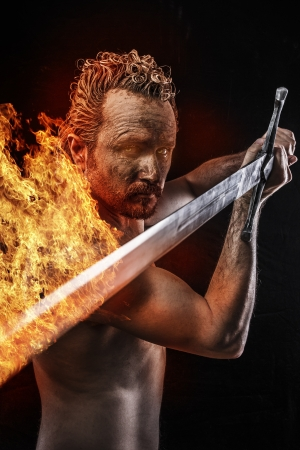 Strong warrior licking a big sword in fire, covered in mud and naked Standard-Bild