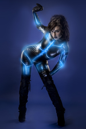 Young sexy latex woman on future costume, blue neon lights Stock Photo