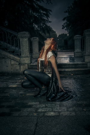 Under the storm, beautiful vampire woman in palace gate, rain photo