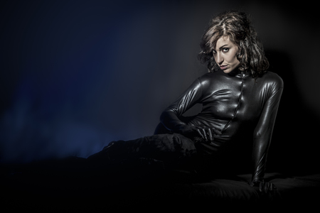 Beautiful brunette woman wearing latex dress on dark background, lying photo