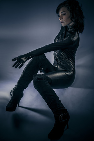 latex woman: Young sexy latex woman on blue background