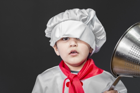 Childhood, Little boy preparing healthy food on kitchen over grey background, cook hat photo