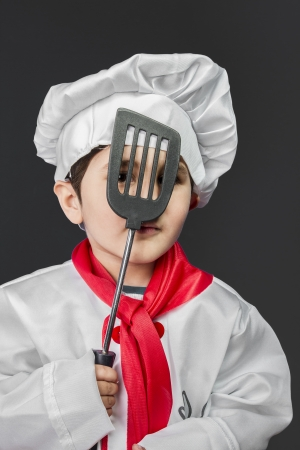 Cooking, Little boy preparing healthy food on kitchen over grey background, cook hat photo