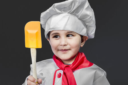 Little boy preparing healthy food on kitchen over grey background, cook hat photo