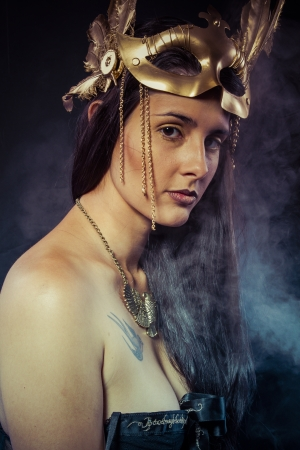 Warrior woman with gold mask, long hair brunette. Long hair. Profile. Studio shot photo