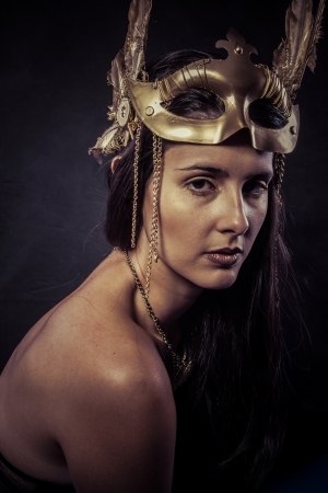 Valkyrie, Golden statue concept. Arty portrait of model with golden mask and shiny lashes. Perfect sporty body. Long hair. Profile. Female photo