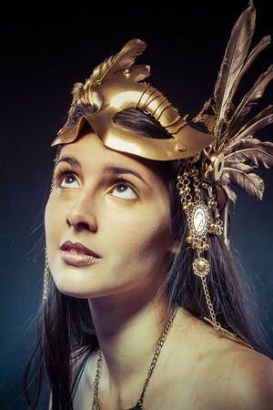 Vintage warrior woman with gold mask, long hair brunette. Long hair. Profile. Studio shot photo