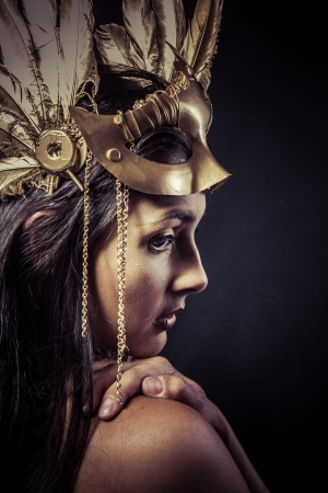 Valkyrie, Golden statue concept. Arty portrait of model with golden mask and shiny lashes. Perfect sporty body. Long hair. Profile. glamour photo