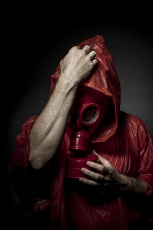 Problem, A man in a gas mask over  the smoke. black background and red colors photo