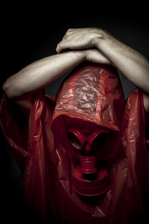 Risk, A man in a gas mask over  the smoke. black background and red colors photo
