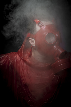 Destruction, A man in a gas mask over  the smoke. black background and red colors Stock Photo - 24886218
