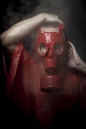 Cloak, A man in a gas mask over  the smoke. black background and red colors photo