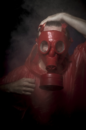 Pollution, A man in a gas mask over  the smoke. black background and red colors photo