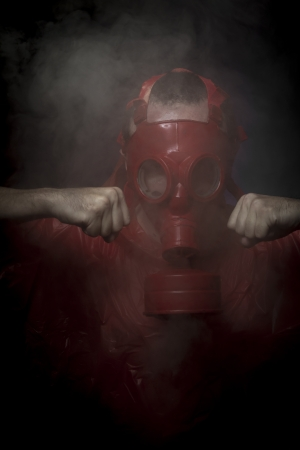 Radioactivity, A man in a gas mask over  the smoke. black background and red colors photo